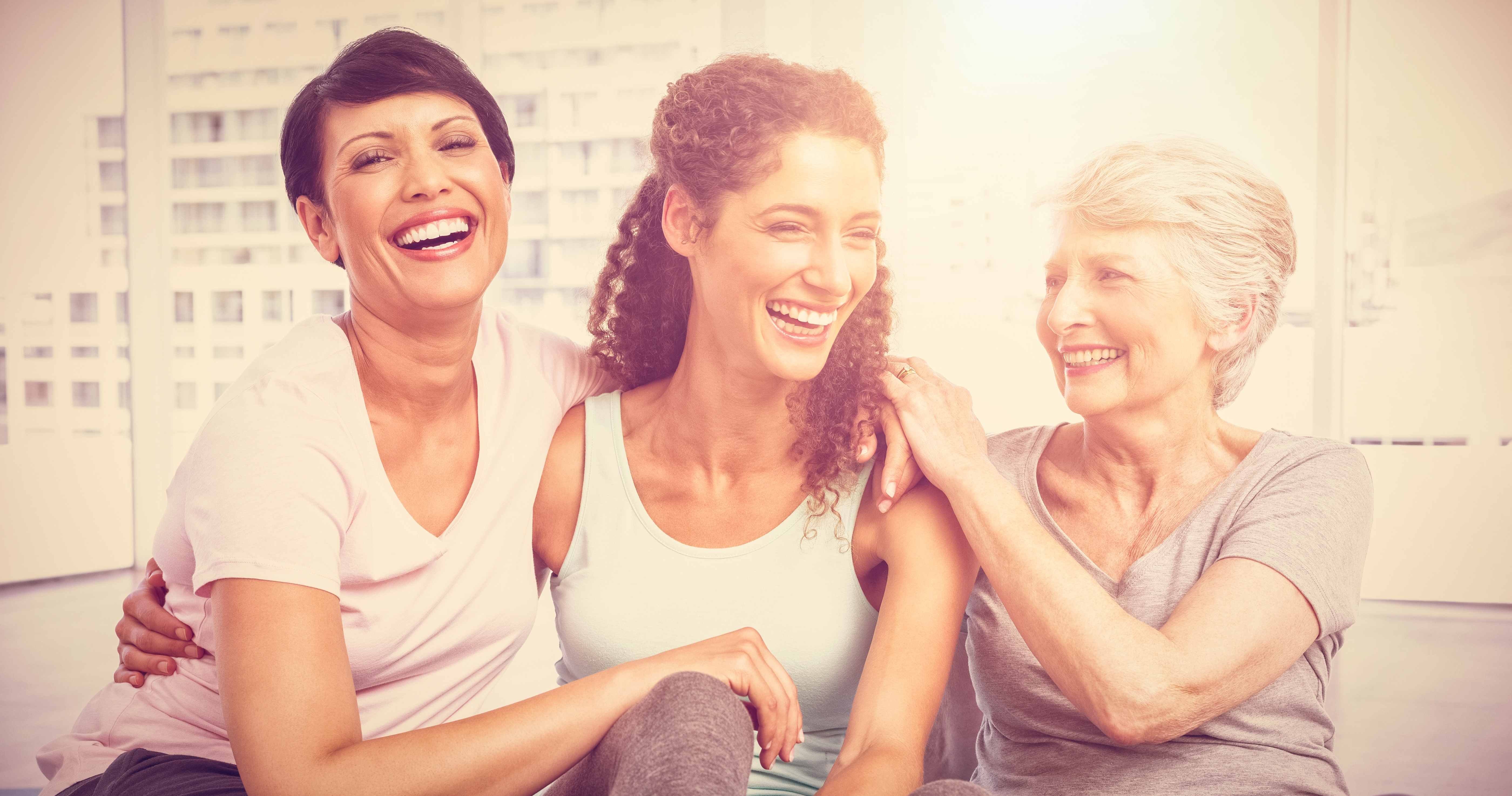 Three women hugging and laughing